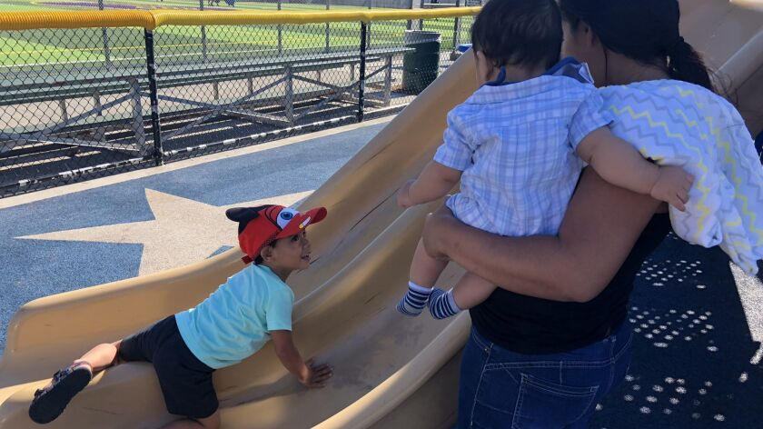 Claudia Calderon plays with her her sons, Andriy, 3, and Adrian, seven months, at a park in Van Nuys