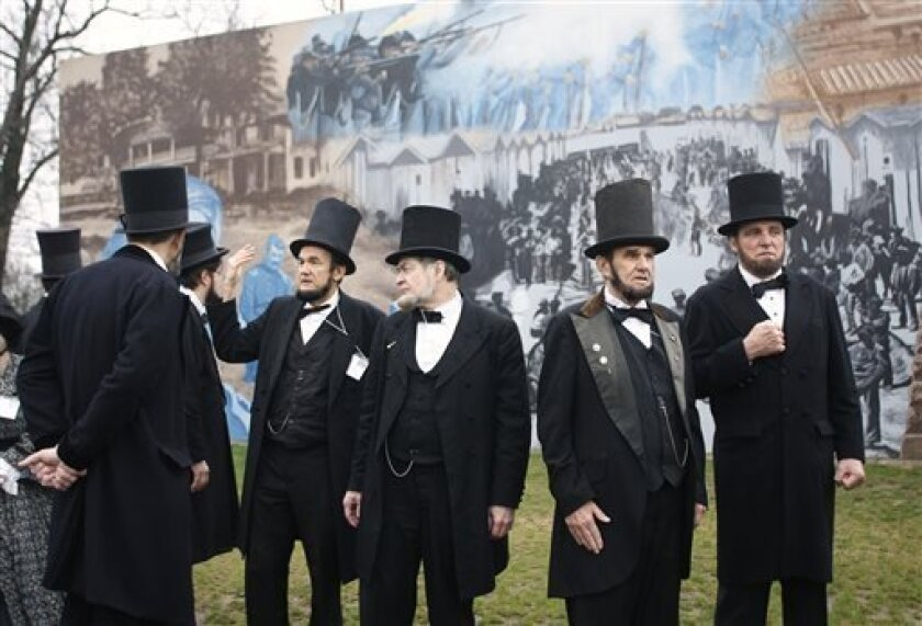 Members of the Association of Lincoln Presenters visit a Civil War mural on their way to the Ohio Statehouse on Friday, April 12, 2013 in Columbus, Ohio. They were going there to hear a Lincoln speech in the House chamber given by fellow presenter Jerry Payn. About three dozen Abraham Lincoln impersonators from around the U.S. are convening in Columbus for their 19th annual convention to compare notes and costumes and tour some Abe-related historical sites. (AP Photo/Mike Munden)