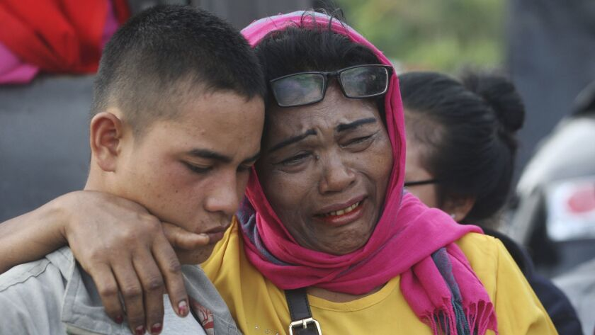 Relatives of victims of a sunken ferry weep as they wait for news at the Tigaras port in Toba lake,
