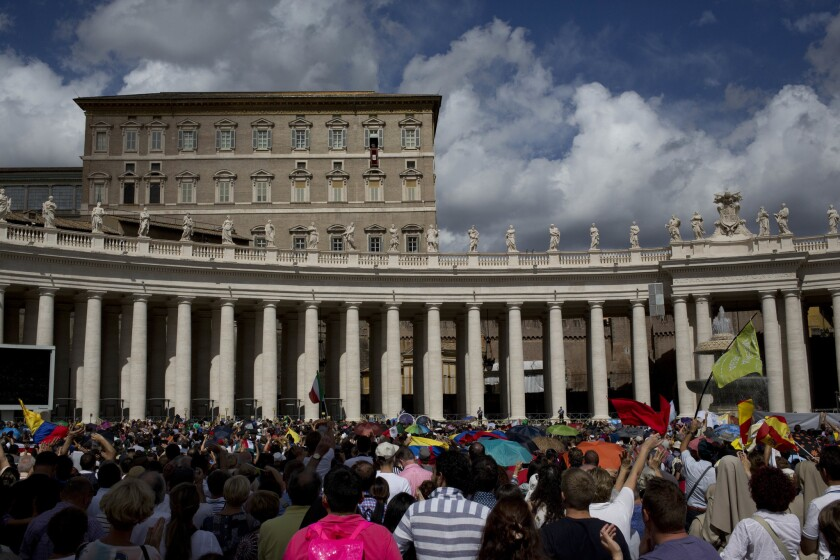 El papa Francisco (asomado por la ventana de su despacho, segundo desde la derecha de la planta superior) preside la oración del Angelus el domingo 18 de septiembre de 2016 a los reunidos en la Plaza de San Pedro, en el Vaticano. (AP Foto/Alessandra Tarantino)