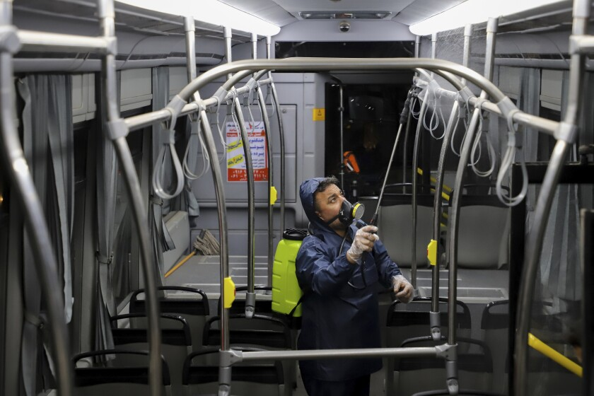 A worker disinfects a public bus against coronavirus in the early morning of Feb. 25 in Ahvaz, southwestern Iran.