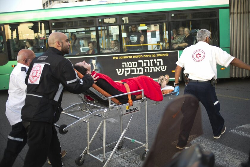 Israeli rescue personal evacuate a woman from a stabbing attack site in Rishon Lezion, Israel, Monday, Nov. 2, 2015.  Israel's emergency rescue service said two people were seriously injured and one lightly in the attack in Rishon Lezion near Tel Aviv. (AP Photo/Ariel Schalit)