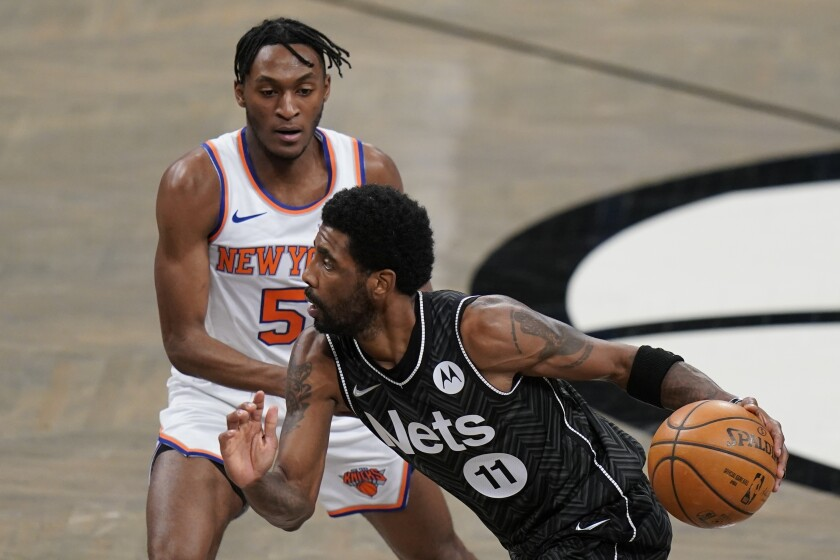 Brooklyn Nets' Kyrie Irving (11) drives past New York Knicks' Immanuel Quickley (5) during the first half of an NBA basketball game Monday, March 15, 2021, in New York. (AP Photo/Frank Franklin II)