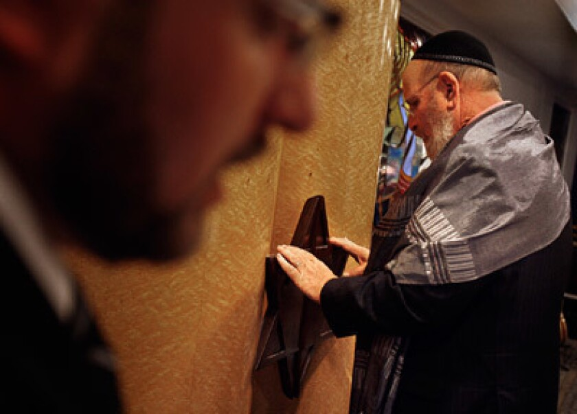 Rabbi Mark Borovitz, right, holds onto the Star of David while focusing himself during a prayer being said during Shabbat services at Beit T'Shuvah, a Jewish residential rehabilitation center that has about 120 residents in treatment on a consistent basis. Audio slide show: Breaking the chains of addiction.
