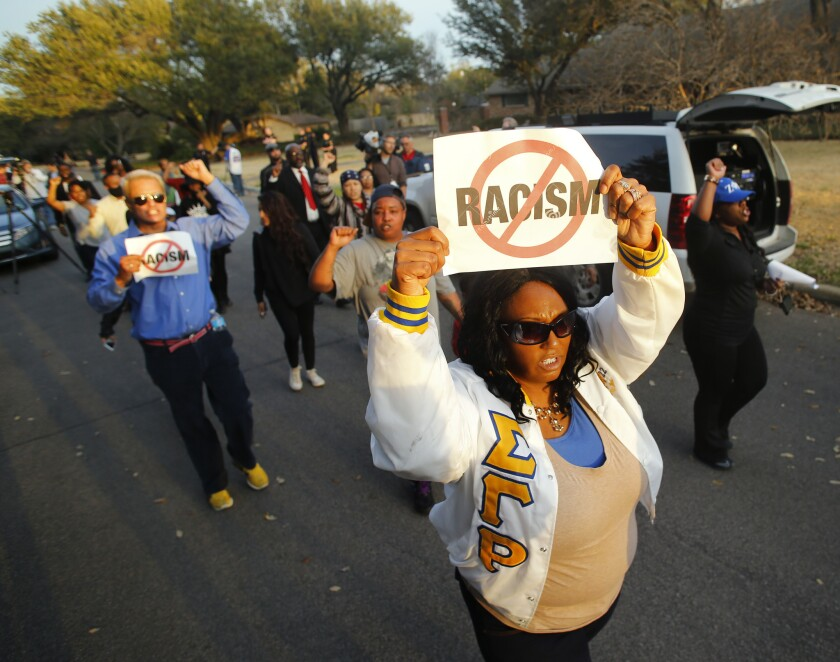 Darmita White protests outside of the home of Parker Rice, one of two students expelled from the University of Oklahoma for leading a racist fraternity song in a video.