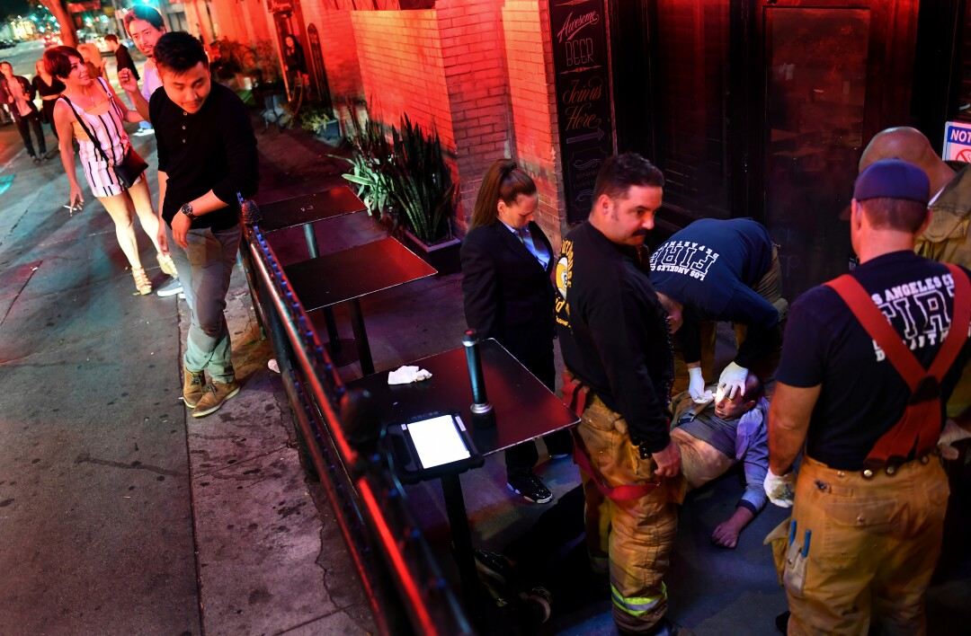 Firefighters treat an unconscious person outside Cole's French Dip in downtown Los Angeles