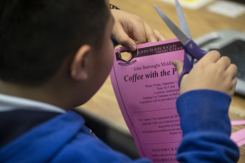 A Burroughs Middle School student in a class for students with special needs cuts out a flyer.