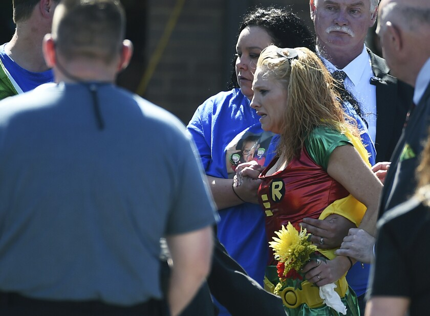 Renae Hall, right, mother of Jacob Hall, reacts as her son is placed into a hearse during his superhero-themed funeral.