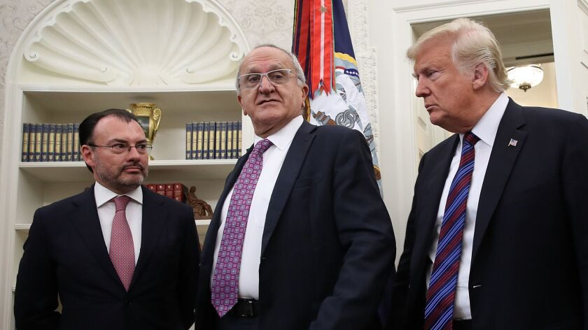 Mexican Foreign Secretary Luis Videgaray, left, and Jesus Seade, representative in the trade talks of Mexican President-elect Andres Manuel Lopez Obrador, gather with President Trump in the Oval Office for a call Monday between Trump and Mexican President Enrique Peña Nieto.