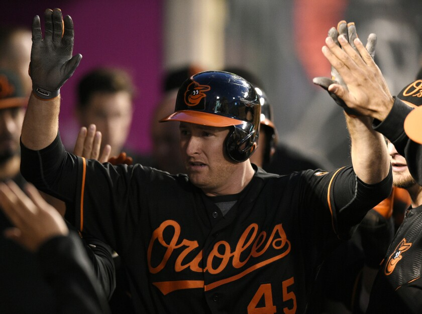 Orioles outfielder Mark Trumbo celebrates with his teammates after hitting a two-run home run during a game on May 20 at Angel Stadium.