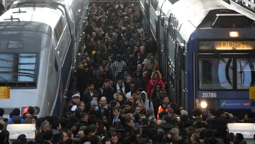 Commuters stand on a crowded platform of the Gare de Lyon railway station in Paris on Tuesday, the first day of a two-day strike.