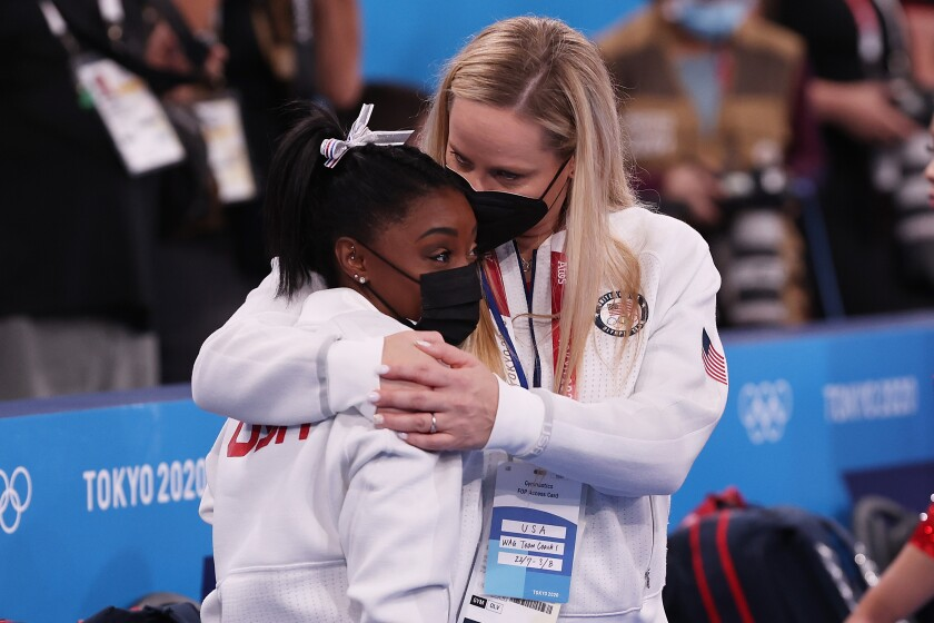 Simone Biles is embraced by coach Cecile Landi during the Women's Team Final at Tokyo Olympics.