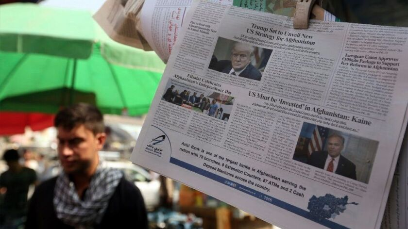Newspapers hang for sale at a stand carrying headlines with photo of the U.S. President Donald Trump