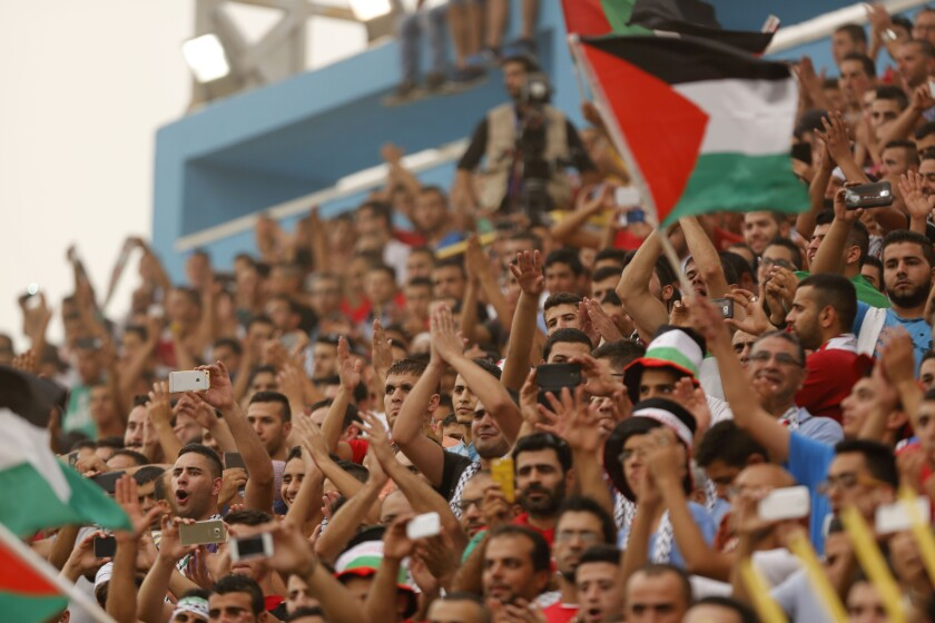 FILE - In this Sept. 8, 2015 file photo, Palestinian fans cheer during a World Cup soccer qualifying match between the Palestinian and the UAE teams at the Faisal al-Husseini stadium in the West Bank town of Al-Ram. Israel has denied travel permits to most players on a Gazan soccer team which had hoped to cross through Israel and into the West Bank to play a local championship final against a rival Palestinian club. Khadamat Rafah is set to play Balata FC in the West Bank on Wednesday, Sept. 25, 2019. But without the hard-to-obtain Israeli travel permits, the game is unlikely to take place as scheduled. (AP Photo/Majdi Mohammed, File)