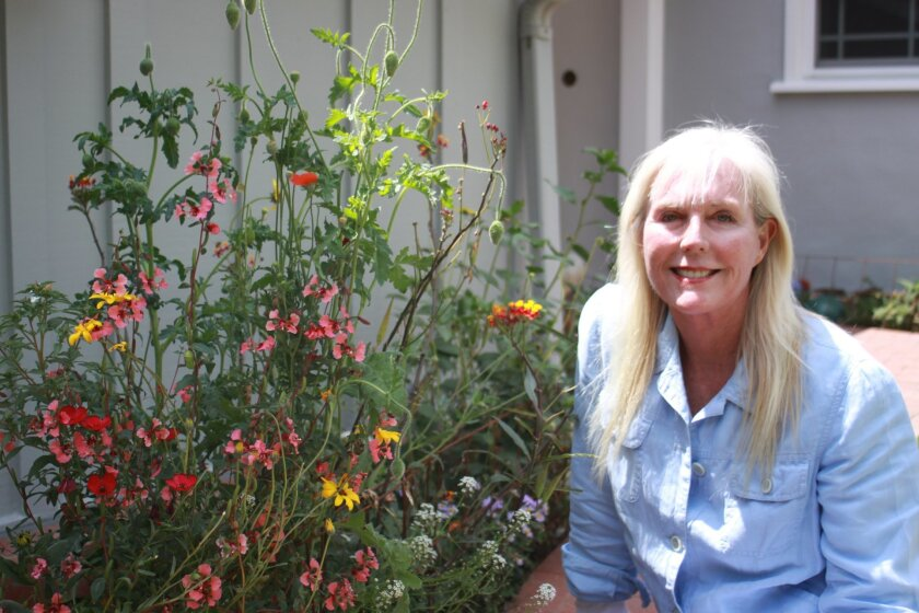 La Jollan Mary Ellen Morgan next to her garden, which contains the monarch butterfly host plant milkweed