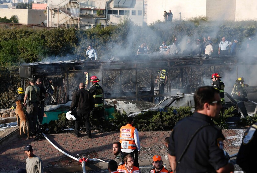 Israeli security forces and emergency services gather around a burned-out bus after an attack in Jerusalem on Monday.