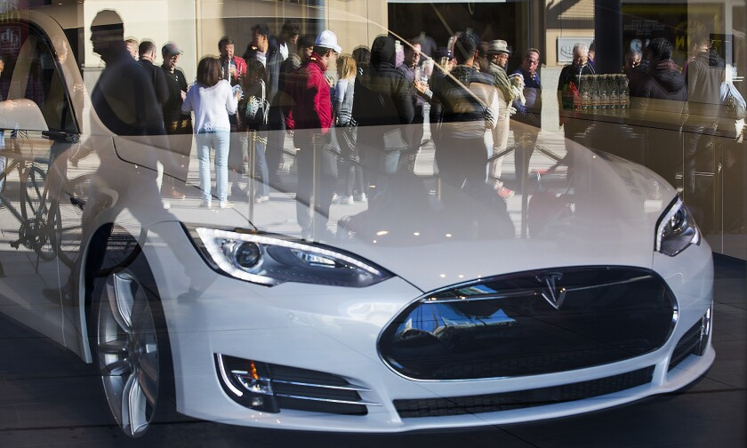 Prospective customers for Tesla's Model 3 sedan are shown in the reflection of a Model S at a Santa Monica showroom in 2016. Hundreds waited in line to put down $1,000 deposits and get on the delivery list for the new car.
