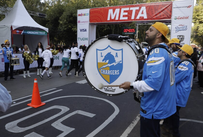 The Chargers' Thunderbolt Drumline and Lightning Crew greet runners at the finish line for a fan race in Mexico City on Nov. 17, 2019.