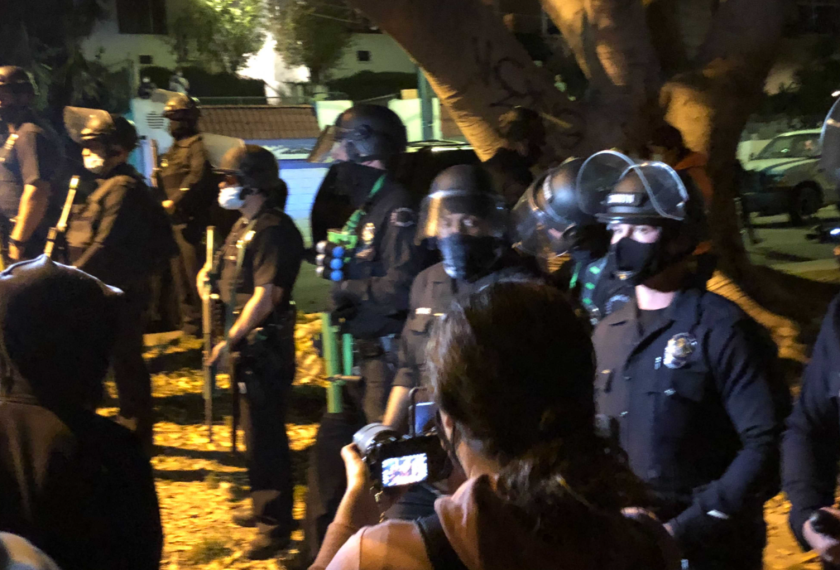 A line of police in riot helmets and holding projectile weapons