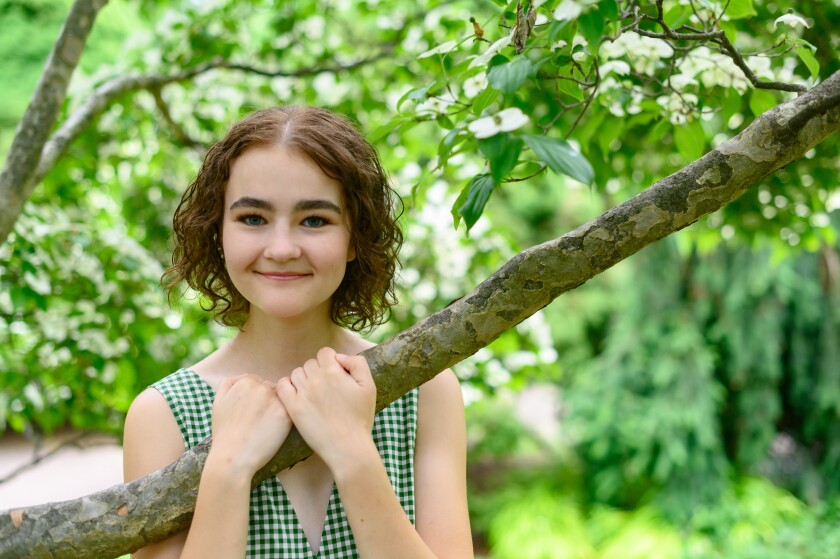 Millicent Simmonds grabs hold of a tree branch.
