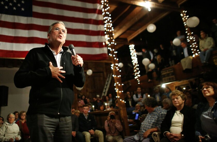 In this Nov. 3, 2015, photo, Republican presidential candidate, former Florida Gov. Jeb Bush, left, addresses an audience at a campaign event held in a barn belonging to former Sen. Scott Brown, R-Mass., in Rye, N.H. Bush is raising his voice, and has a new rasp in his voice to show for it after a