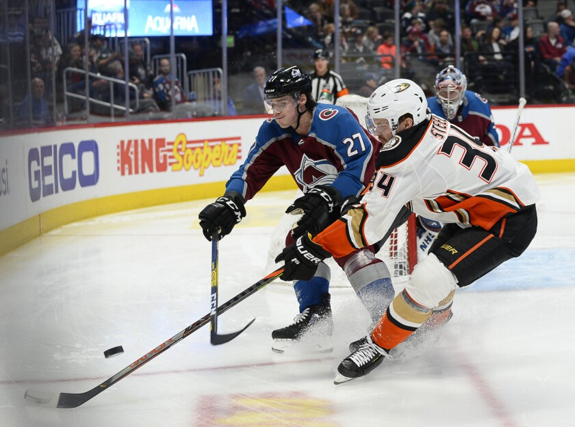 Avalanche defenseman Ryan Graves and Ducks center Sam Steel chase a puck into a corner during the second period of a game March 4 at the Pepsi Center.