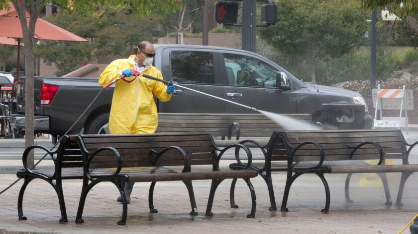 Alberto Ruiz, with National Maintenance Services, sprayed a bleach solution on benches at Promenade Park in El Cajon Thursday to fight an ongoing hepatitis outbreak that has sickened more than 30 people in the East County city.
