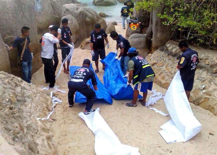 Thai emergency workers secure the bodies of two British tourists on Koh Tao island on Sept. 15, a double slaying that threatens to further damage the country's tourism industry after a year of unrest and a military coup.