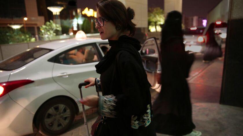 RIYADH, SAUDI ARABIA--APRIL 22, 2015--A woman waits for an Uber taxi at Kingdom Center shopping mall