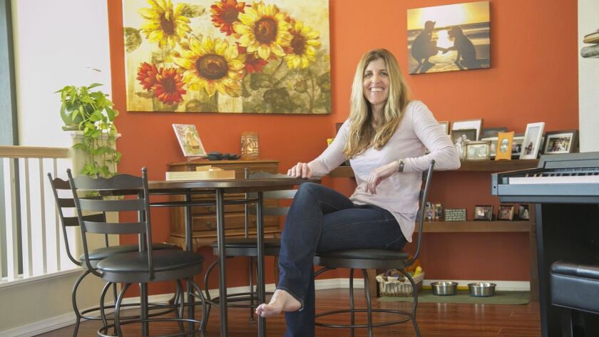 """Author Susan Hannifin-MacNab in the dining room of her home in Carmel Mountain Ranch. After losing her husband in a car accident in 2012, she wrote the """"A to Z Healing Toolbox"""" guide to grief recovery."""