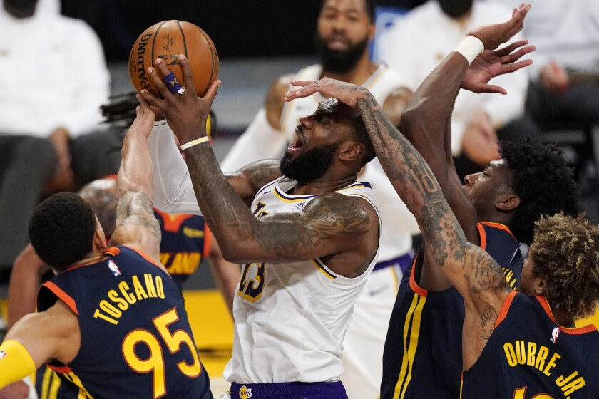 Los Angeles Lakers forward LeBron James, second from left, is fouled by Golden State Warriors guard Kelly Oubre Jr., right, while shooting as forward Juan Toscano-Anderson, left, and guard Jordan Poole defend during the first half of an NBA basketball game Sunday, Feb. 28, 2021, in Los Angeles. (AP Photo/Mark J. Terrill)