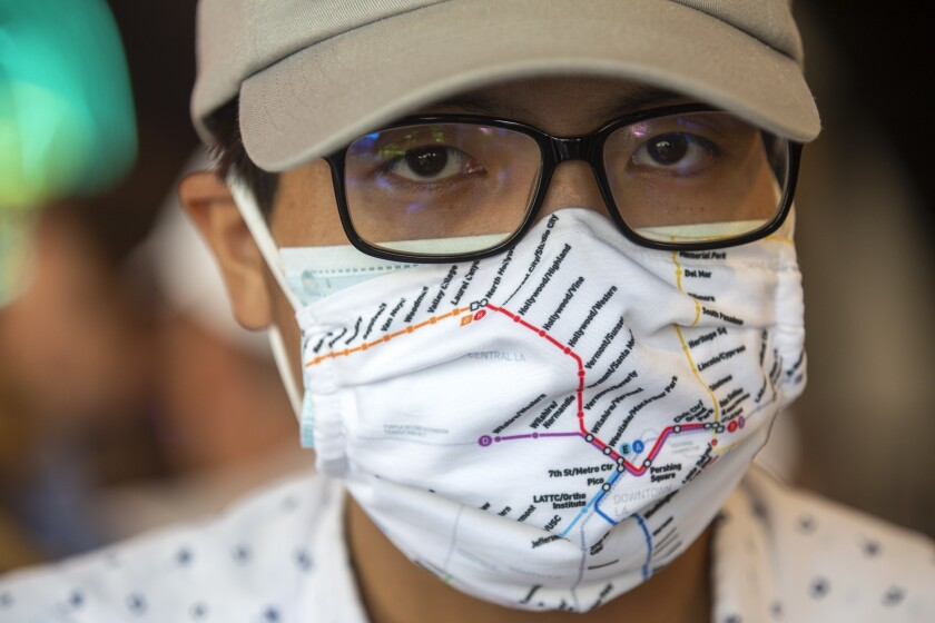 """Transit """"superfan"""" Kenny Uong wears a mask showing a map of Metro rail lines."""