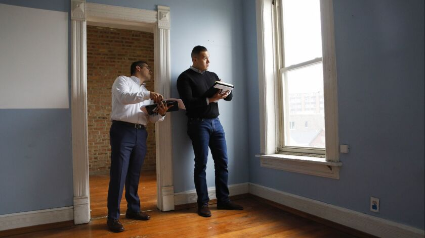 Gabriel Villagomez, right, works with real estate broker and consultant Miguel Chacon at a property in Chicago on June 12.
