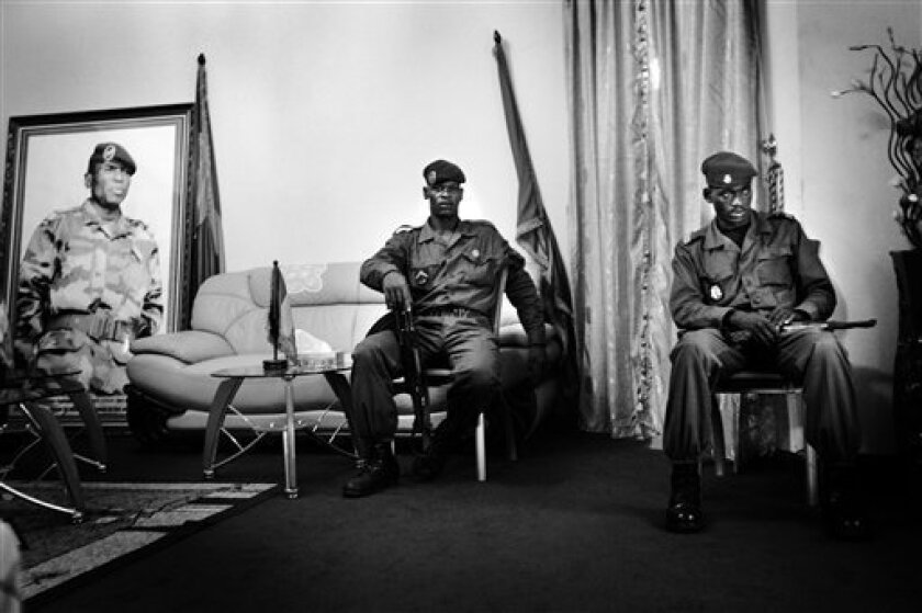 """Guinea Conakry soldiers sit near a giant portrait of military junta leader Capt. Moussa """"Dadis"""" Camara in a waiting room adjacent to his bedroom at a military camp in Conakry Monday March 9, 2009.  The modesty that characterized his first weeks in office has been replaced by a Messianic tone. Wall-"""