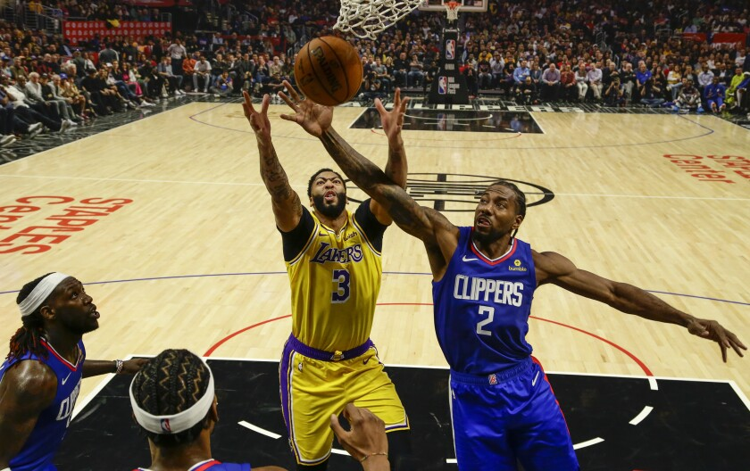 Lakers forward Anthony Davis (3) and Clippers forward Kawhi Leonard (2) battle for a rebound during the season-opening game Tuesday.
