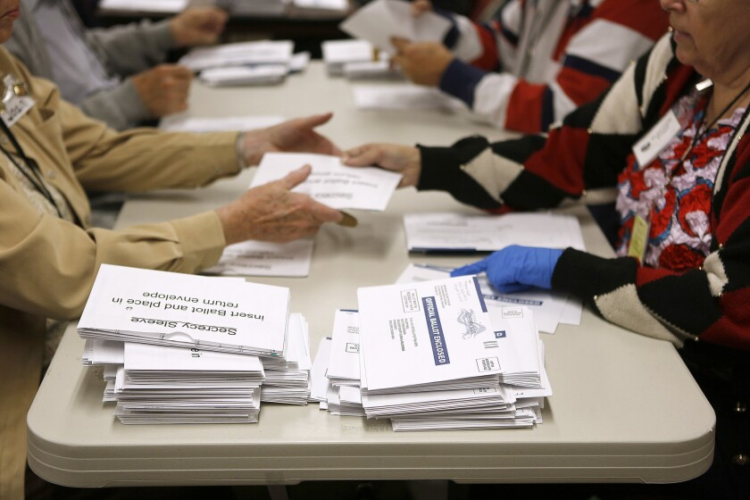 Election workers in Colorado open mail-in ballots.