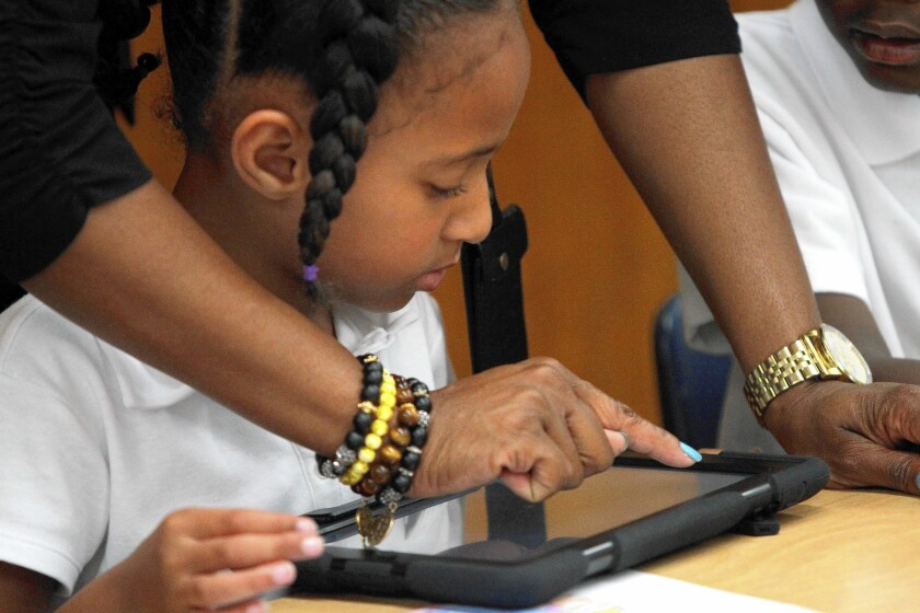 A student gets help as she and her teacher explore the possibilities with new Apple iPads provided by the Los Angeles Unified School District.