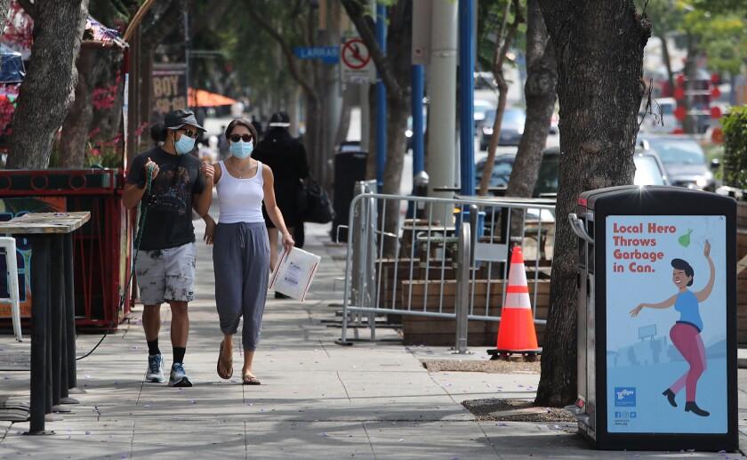 A man and a woman, both wearing masks, walk along Santa Monica Blvd. in West Hollywood.