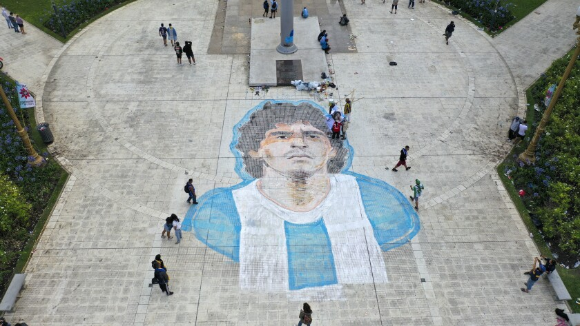People walk past mural of Diego Maradona painted on the Plaza de Mayo in front of the presidential palace in Buenos Aires.