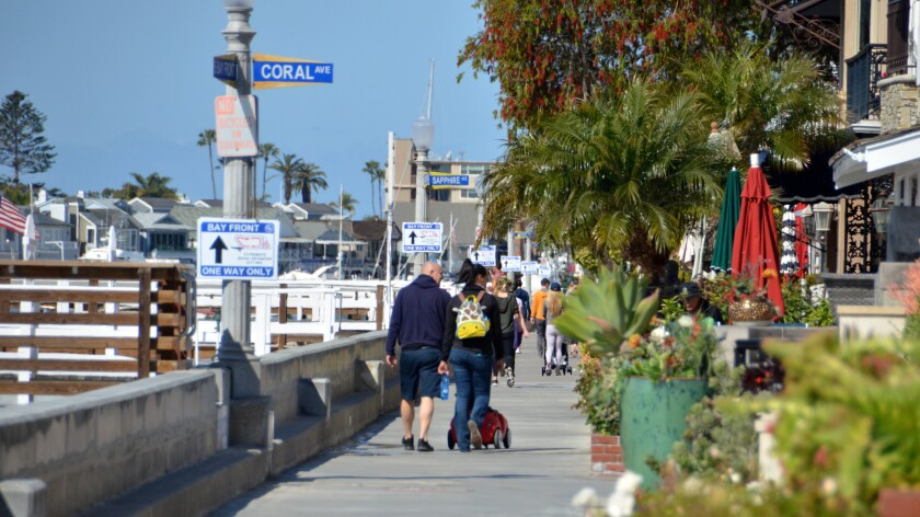 Groups of people obeying the one-way signs, make their way around Balboa Island on March 28.