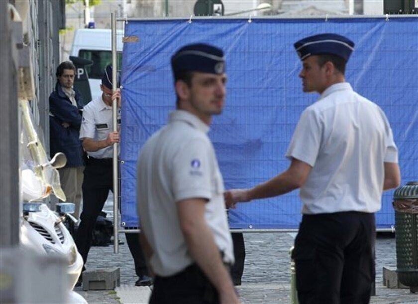 Police officers block off a crime scene in Brussels, Belgium,Thursday, June 3, 2010. A gunman entered a Brussels courtroom Thursday and killed a justice of the peace and a court clerk, then left the courthouse on foot, officials said. (AP Photo/Yves Logghe)