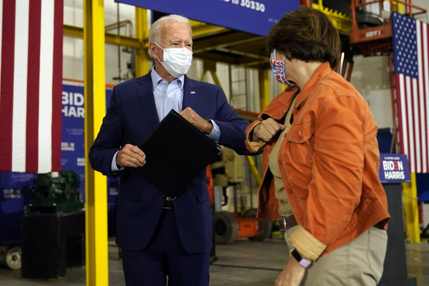 Joe Biden bumps elbows with Sen. Amy Klobuchar (D-Minn.) in Hermantown, Minn.