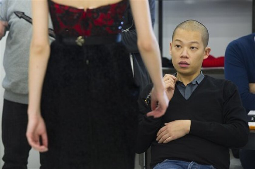 """In this Feb. 7, 2012 photo, designer Jason Wu attends a model fitting in preparation for his Fashion Week show, in New York. Casting and fitting models for a fashion show is more art than science, but, says designer Jason Wu, there's still a formula. """"It's like match-making,"""" he said. """"It has to fit."""" (AP Photo/Charles Sykes)"""
