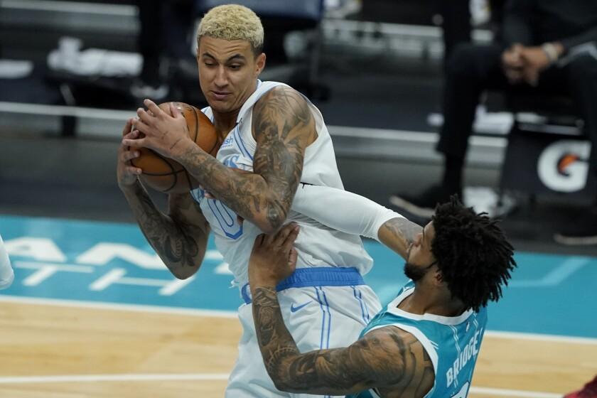 Lakers forward Kyle Kuzma pulls a rebound away from Charlotte Hornets forward Miles Bridges .