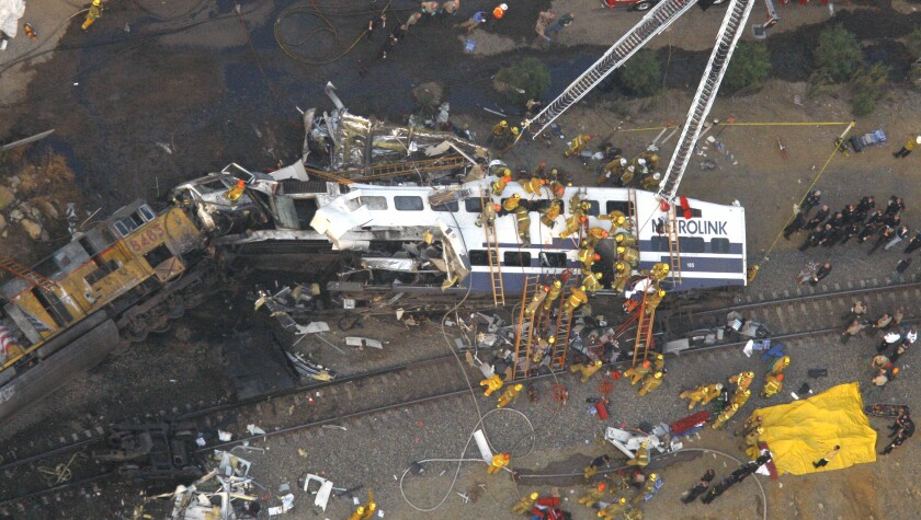 Aerial view of firefighters and rescuers around the wreckage of two trains on their sides after a head-on collision
