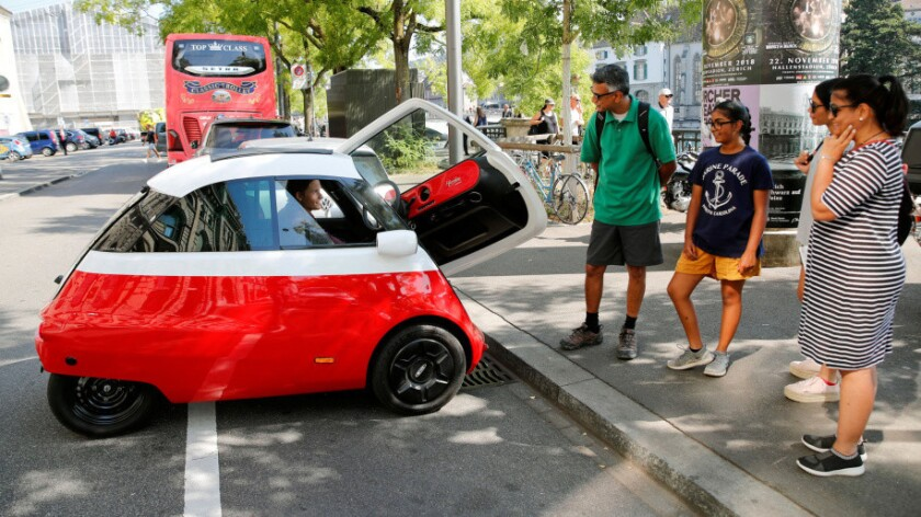 Chief Marketing Officer Merlin Ouboter (L) of Swiss Microlino AG sits in an electric-powered Microlino car as he answers questions of tourists from the United States in Zurich, Switzerland August 16, 2018. REUTERS/Arnd Wiegmann