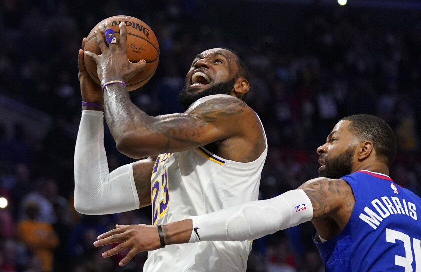 Lakers forward LeBron James, left, shoots in front of Clippers forward Marcus Morris during the second half of the Lakers' 112-103 victory at Staples Center on Sunday.