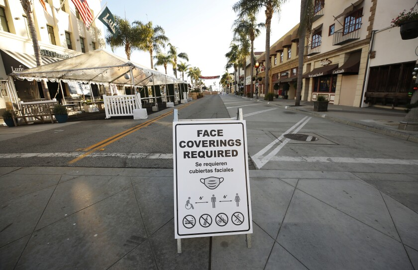 "A sign in in front of shops in Ventura reads, ""Face coverings required"""
