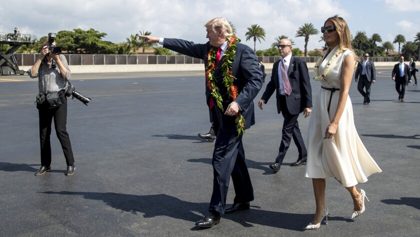 President Trump and First Lady Melania Trump wear leis as they arrive at Joint Base Pearl Harbor Hickam on Friday.