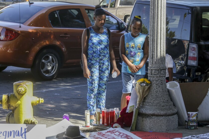 Patricia Thomas, 11, left, and Raquel Thomas, 9, pay their respects at a makeshift memorial for their father, Reginald Thomas, who died after being Tasered by Pasadena police.